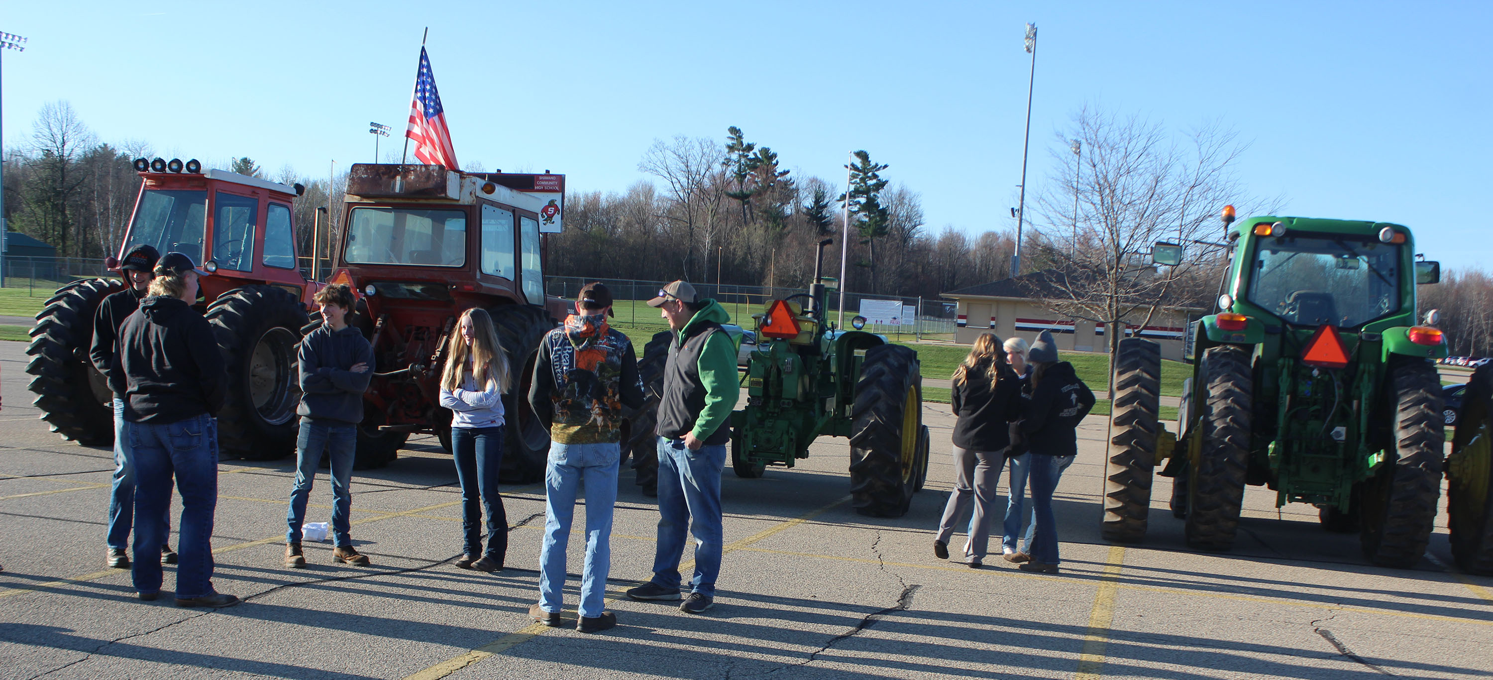 Shawano FFA members congregate and chat before school on April 17 as their tractors are parked nearby in the Shawano Community High School north parking lot. Once a year, the local FFA chapter holds its Drive Your Tractor to School Day.<br />(Lee Pulaski | NEW Media)