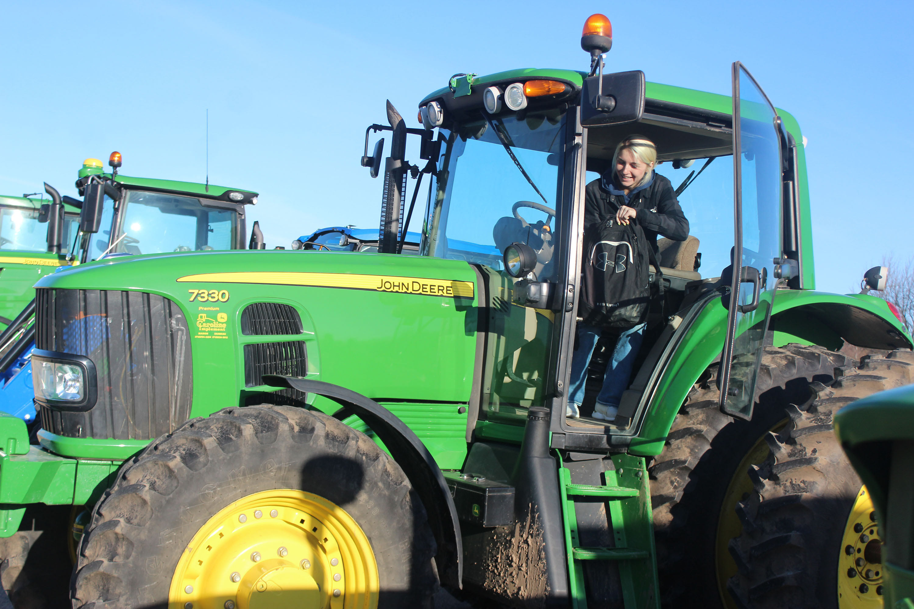 Shawano Community High School senior Kendra Kristof grabs her backpack before climbing out of the cab of her John Deere tractor on April 17 in the high school's parking lot. Kristof joined other Shawano FFA members in participating in the chapter's Drive Your Tractor to School Day, which also included a tractor parade to Hillcrest Primary School and Olga Brener Intermediate School. (Lee Pulaski | NEW Media)