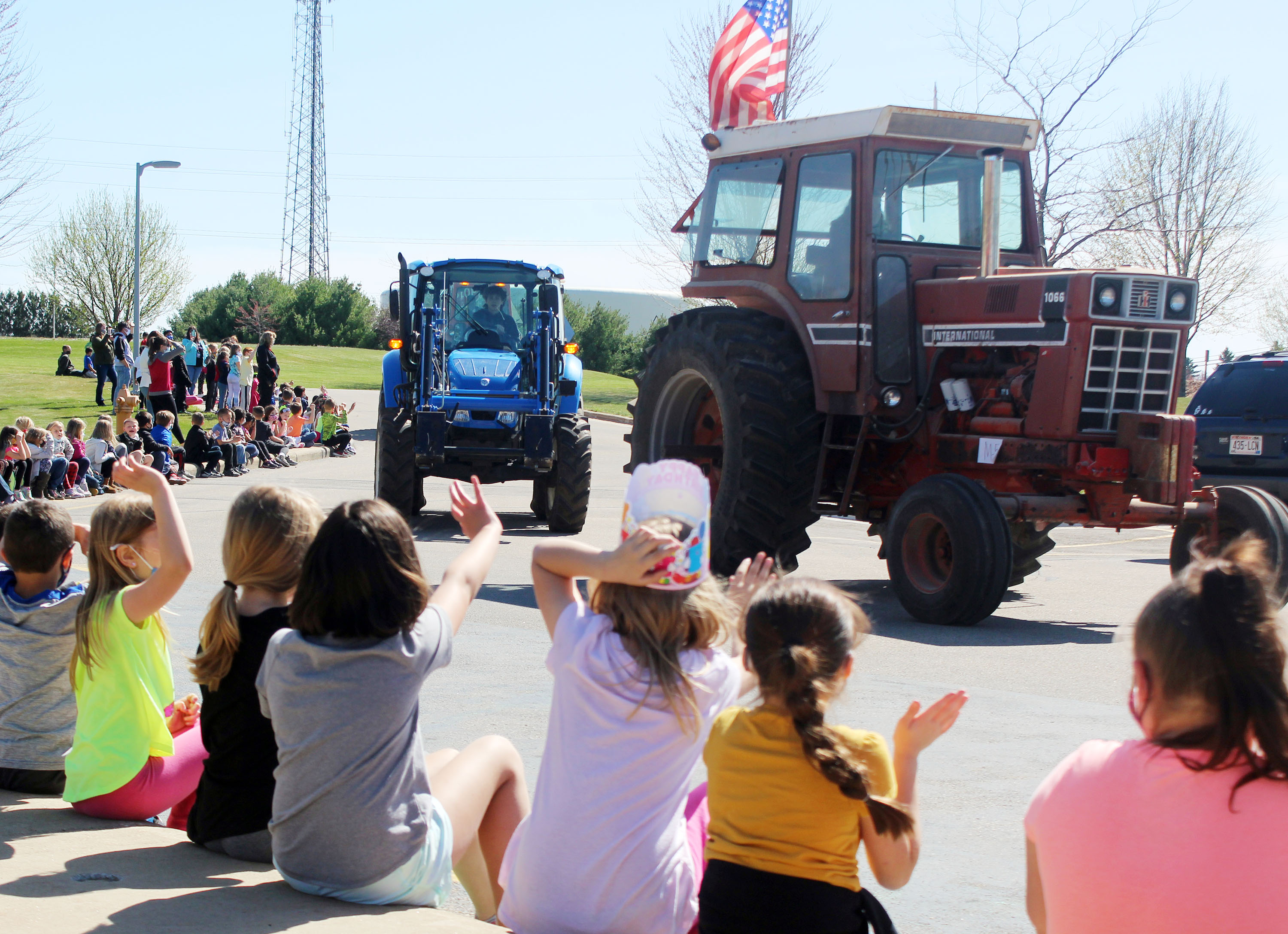 Students at Hillcrest Primary School wave excitedly April 16 as tractors driven by Shawano FFA members roll through Hillcrest's parking lot in a parade. The event was part of the Drive Your Tractor to School Day event.<br />(Lee Pulaski | NEW Media)