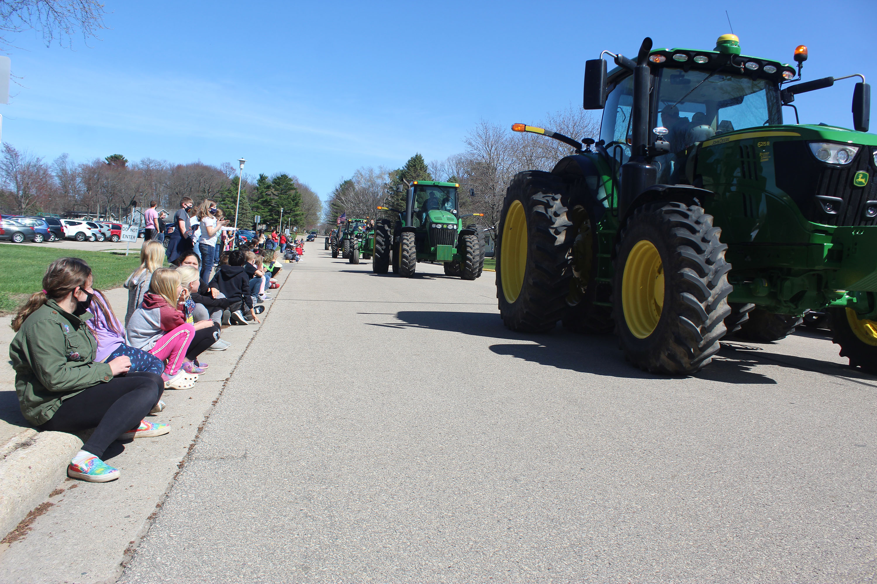 Shawano FFA members roll along in front of Olga Brener Intermediate School in a parade on April 16 as students wave and cheer them on. The visit capped off the FFA's Drive Your Tractor to School Day.<br />(Lee Pulaski | NEW Media)